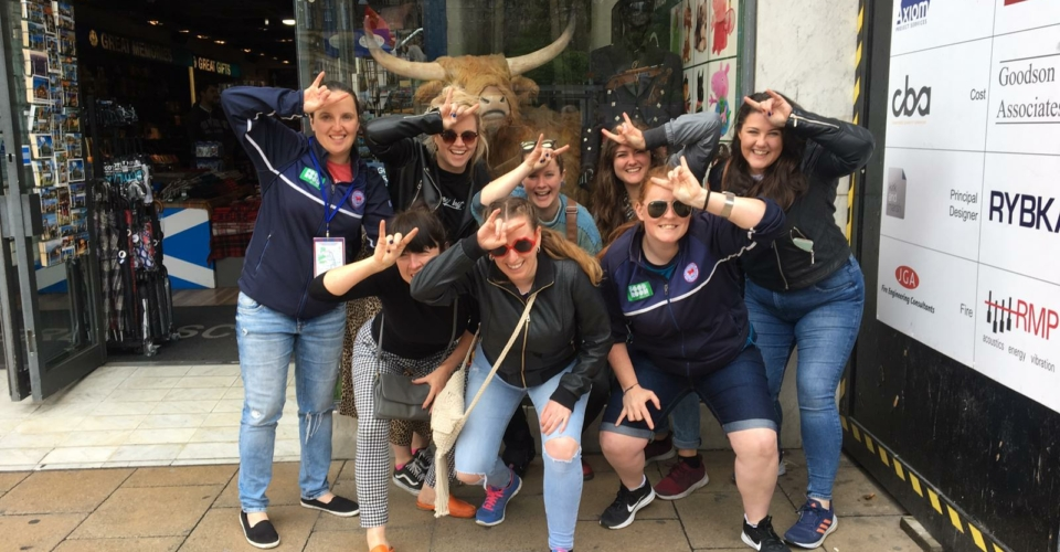 Clontarf Women's Rugby team making bull sign above their heads in front of a shop